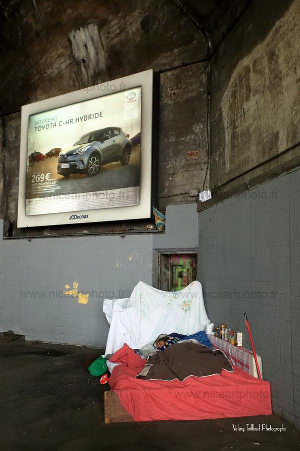 Personne sans domicile fixe allongée sur un lit improvisé sous une enseigne publicitaire